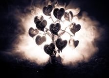 Abstract field with tree and hearts on it behind dark foggy toned sky. Love tree of dreams. Valentine concept background. Selective focus Stock Photos