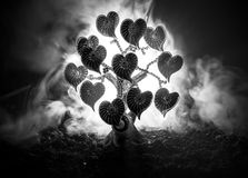 Abstract field with tree and hearts on it behind dark foggy toned sky. Love tree of dreams. Valentine concept background. Selective focus Royalty Free Stock Photo