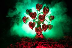 Abstract field with tree and hearts on it behind dark foggy toned sky. Love tree of dreams. Valentine concept background. Selective focus Stock Photography