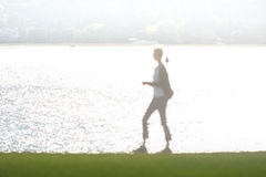 Abstract figure of woman walking by water Royalty Free Stock Image