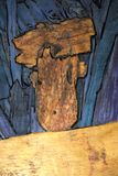 Abstract figures on a wooden board, which were already present on the wood and are highlighted in color and stock images