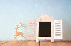 Abstract filtered photo of decorative chalkboard frame and wooden deer over wooden table. ready for text or mockup.  Royalty Free Stock Images