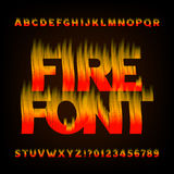 Abstract fire alphabet font. Flame effect letters and numbers on a dark background. Royalty Free Stock Images