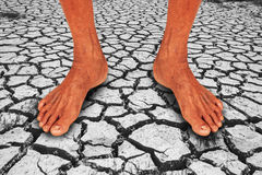 Abstract ,foot of elderly man standing on earth crack Stock Image