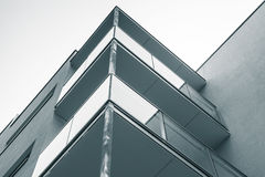 Abstract fragment of modern block of flats. Abstract fragment of modern architecture, concrete walls and glass of balconies. Blue toned photo background Stock Photography