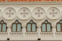 Abstract French balconies which decorated in circle shape above. Arch door on stucco wall background Royalty Free Stock Photography