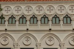 Abstract French balconies which decorated in circle shape above. Arch door on stucco wall background Stock Image