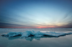 Abstract frozen winter sunrise seascape with ice and colored the sky. Royalty Free Stock Photography