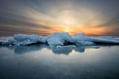 Abstract frozen winter sunrise seascape with ice and colored the sky. Stock Photography