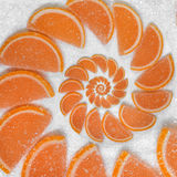 Abstract fruit jelly wedges orange cantle lobule on white sugar background. Orange jellies. Sweet fruit segments. Juicy fruit jell. Y on sugar sand Abstract food Royalty Free Stock Image