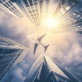 Abstract futuristic cityscape view with airplane flying above mo Stock Photography