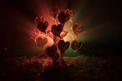 Abstract gebied met boom en harten op het achter donkere mistige gestemde hemel Liefdeboom van dromen de achtergrond van het vale Royalty-vrije Stock Afbeeldingen