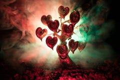 Abstract gebied met boom en harten op het achter donkere mistige gestemde hemel Liefdeboom van dromen de achtergrond van het vale Stock Afbeelding
