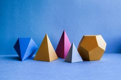 Abstract geometric figures. Three-dimensional dodecahedron pyramid tetrahedron cube rectangular objects on blue. Background. Bright platonic solids still life Stock Photography