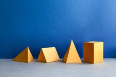 Abstract geometric figures. Three-dimensional pyramid tetrahedron cube rectangular objects on blue gray background. Yellow color Platonic solids still life Stock Photos