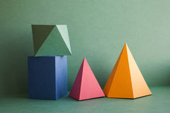 Abstract geometrical solid figures still life. Colorful three-dimensional pyramid prism rectangular cube arranged on. Green background. Yellow blue pink royalty free stock photos