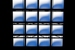 Abstract geometrics of a skylight. Bleuish light shining through the opaque glass in a high atrium skylight royalty free stock photo