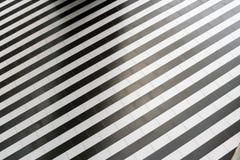 Abstract geometrisch patroon van regelmatige afwisselende zwart-witte strepen op de vloer Stock Foto