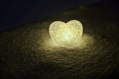 Abstract glass heart on snow at night. Card for a Valentine`s day. blue heart llight on black background Royalty Free Stock Photos