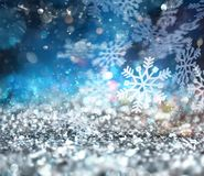 Abstract glowing Christmas blue background with snowflakes. With light effect stock illustration