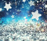Abstract glowing Christmas blue background with stars. And light effect royalty free illustration