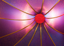 Abstract of a glowing purple lampshade. A close up of a purple silk lampshade that is glowing with lines radiating out of it stock photos