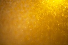 Abstract gold blurred background with numerous colourful bright festive bokeh. Texture with copy space for text. royalty free stock photography