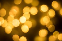 Abstract gold bokeh with black background. The bokeh of Christmas lights black backdrop royalty free stock photos