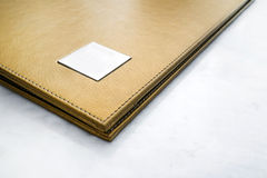 Abstract gold leather menu covered, on white marble stone table Stock Photo
