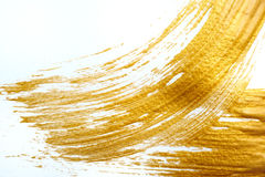 Abstract gold stroke with acrylic paint brush on white background and place for text Stock Images