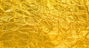 Abstract golden foil background. Panoramic Abstract golden foil background. Crumpled shiny gold foil texture for design. Creative pattern. Luxury Wide angle royalty free stock photo