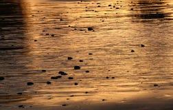 Abstract, gouden zand op een strand bij zonsondergang Stock Foto's