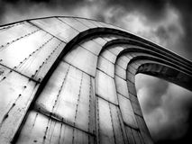 Abstract grand steel rainbow looking to the sky background. Futuristic urban design black and white royalty free stock photography