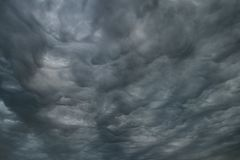 Abstract gray background of the thunderous gloomy cumulus clouds, stormy sky. Abstract gray background of thunderous gloomy cumulus clouds, stormy sky Stock Photos