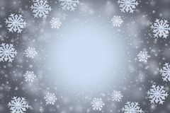 Abstract gray winter background with the snowflakes and copy space in the center. Abstract gray winter background with the snowflakes are arranged in a circle stock photography