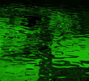 Abstract green background. An abstract green background appearing as reflections from a pool of rippling water as seen through a green filter Stock Photos