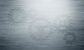Abstract grey polished metal plate with stamped gear icons Stock Images