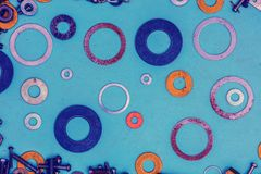 Colorful metallic rings washers on blue wooden background. Abstract grunge background. Colorful metallic rings washers on blue wooden background Stock Images