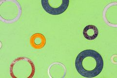 Abstract grunge background. Colorful metallic rings washers on green wooden background Stock Image