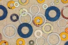 Colorful metallic rings washers on sacking background. Abstract grunge background. Colorful metallic rings washers on sacking background Stock Photos