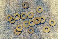 Abstract grunge background. Metallic rings washers on sackcloth Stock Images
