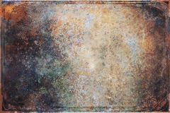 Abstract grunge background texture rusty metal sheet dark burgundy color along the edges, in middle a yellowish speckled blank spa Royalty Free Stock Photo
