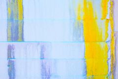 Abstract Grunge Background - white wall with yellow and blue dripping paint and large crack royalty free stock image