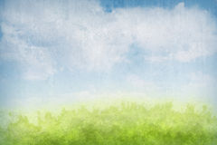 Abstract grunge landscape background. Painterly, abstract landscape with green foliage, blue sky, and clouds Royalty Free Stock Images