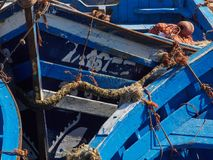 Abstract grunge texture background with slices of the blue wooden fishing boats with ropes, nets and fins. Royalty Free Stock Images