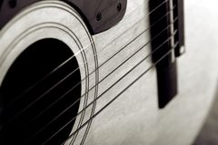 Abstract guitar. Close-up of acoustic guitar; shallow focus; black and white duotone stock image