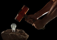 Abstract of hand holding heavy hammer to breaking light bulb on Royalty Free Stock Image