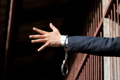 Abstract. Hands of the prisoner on a steel lattice close up. Prison, man in handcuffs. stock photography