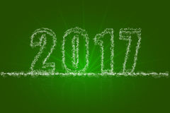 Abstract happy new year 2017 backdrop greeting card. 2017 sign consist of various sized transparent dots, bokeh, circles with beams on green background with Royalty Free Stock Images