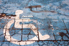 Abstract health sign on with handicapped people symbol pictogam on pavement. Abstract health sign on with handicapped people symbol pictogam on old pavement Stock Photos